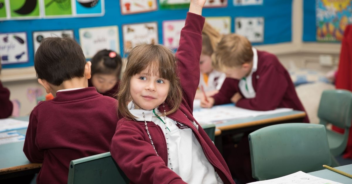 Girl raising her hand in the classroom