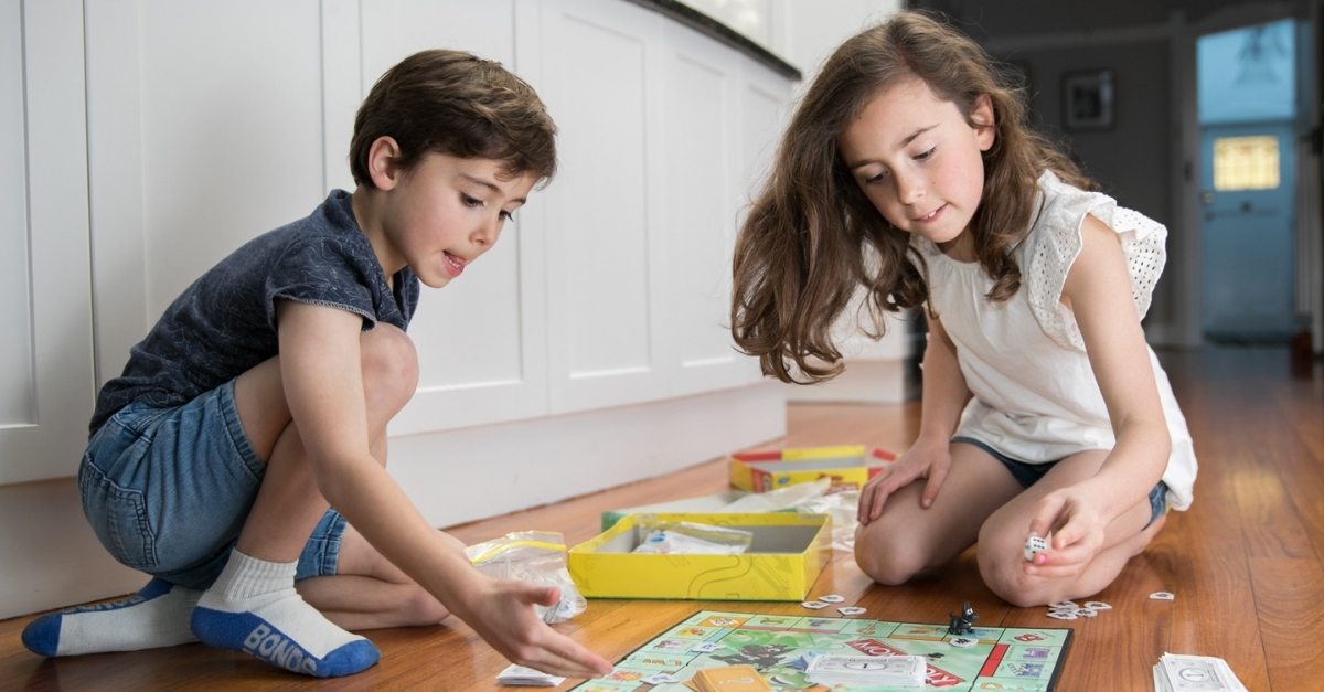 Two children sitting on the floor playing board games together