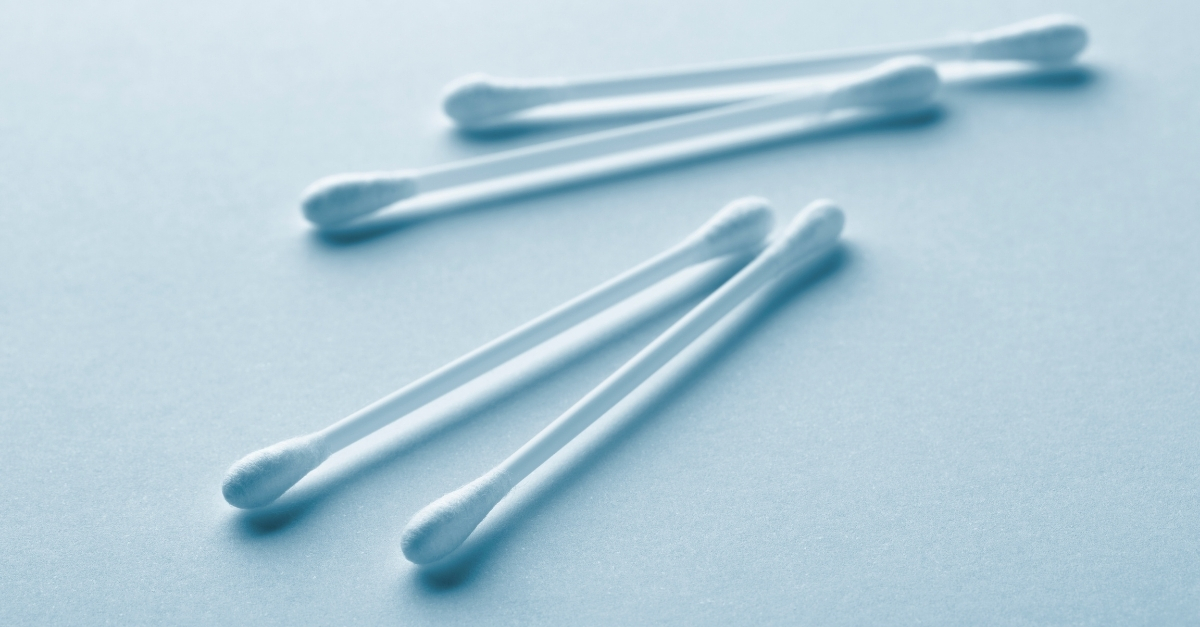 Four cotton buds on white surface