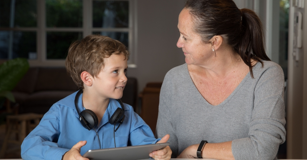 Boy looking up at his mum with iPad in hand and headphones around neck