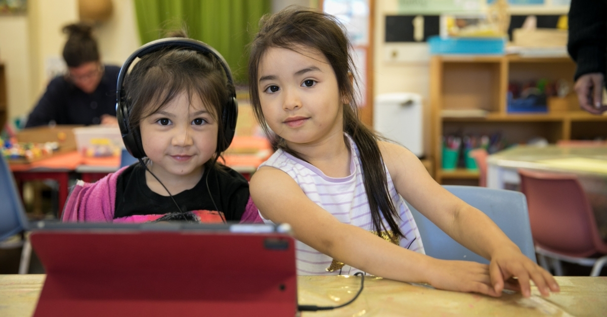 Two girls looking at camera, one with headphones on and tablet in front of her.